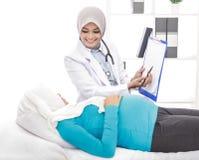 解释诊断的年轻产科医生对她的患者 图库摄影