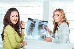 解释诊断的年轻女性医生对她的女性患者 免版税库存图片