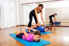 解释年轻男孩健身的老师行使平衡身体 图库摄影