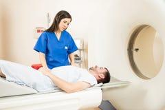 解释CT扫描的护士对患者 库存图片