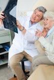 解释X-射线的放射学家对患者 免版税图库摄影