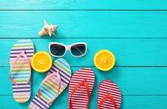 触发器、太阳镜和桔子在蓝色木背景 顶视图和拷贝空间 免版税库存照片