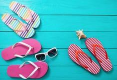 触发器、太阳镜和海壳在蓝色木背景 复制空间和时尚夏天辅助部件 免版税库存图片