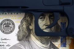 触发在钞票吸引的眼睛的背景的枪 免版税库存照片