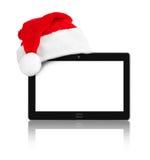触感衰减器个人计算机和圣诞老人红色圣诞节帽子 库存照片