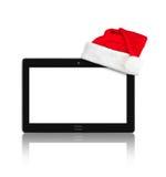 触感衰减器个人计算机和圣诞老人红色圣诞节帽子 库存图片