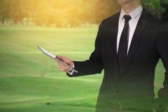 触摸屏在手中在高尔夫球场的商人 会议conferenc 免版税图库摄影
