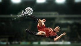 触击球的足球运动员在体育场 免版税图库摄影