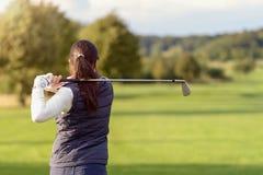 触击高尔夫球的女性高尔夫球运动员 库存图片