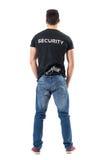 警卫后面看法在简单的衣裳的有在传送带附有的手枪的 免版税库存图片
