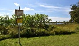 警告关于危险掠食性动物的小心板材在湖Jabiru 免版税库存照片