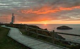 警告号角和木走道在灯塔Peñas海角附近在阿斯图里亚斯,西班牙的美丽的日落海岸 免版税库存照片