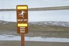 警告在峭壁附近投下标志由水边缘 库存图片