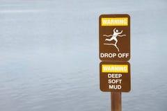 警告在峭壁附近投下标志由水边缘 库存照片