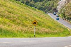 警告陡峭的路标倾斜和卡车在小山 免版税图库摄影