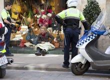警察与无家可归者谈话,坐在橱窗精品店2010年5月10日在巴塞罗那,西班牙 免版税库存照片