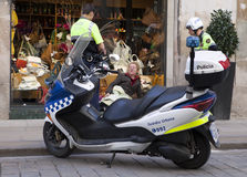 警察与无家可归者谈话,坐在橱窗精品店2010年5月10日在巴塞罗那,西班牙 库存图片