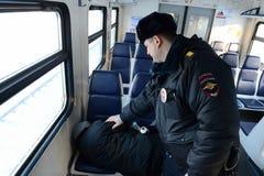 警察叫醒一列市郊火车的一位睡觉的乘客 免版税库存照片