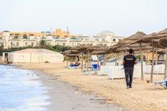 警察在海滩走 免版税库存照片