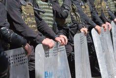 警察在装甲的封销线站立 库存图片