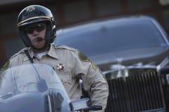 警察坐有汽车的摩托车在背景中 免版税库存照片