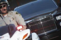 警察坐有汽车的摩托车在背景中 免版税库存图片