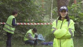 警察妇女的画象绿色制服的在事件的背景在公园,看照相机 股票视频