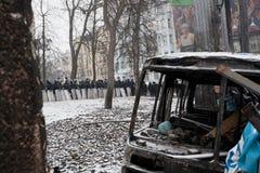 警察小队在等待命令的被烧的公共汽车和护拦后站立对attackon在反政府抗议期间 免版税库存照片