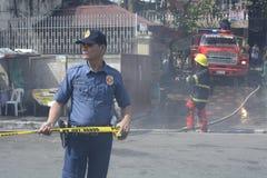 警察帮助维护秩序在毁坏内部简陋小木屋房子的房子火期间 免版税图库摄影