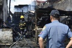 警察帮助维护秩序在毁坏内部简陋小木屋房子的房子火期间 免版税库存图片