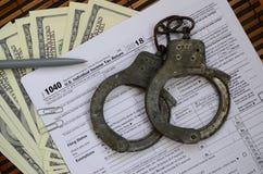 警察手铐在报税表说谎1040 概念的proble 免版税库存图片