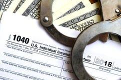 警察手铐在报税表说谎1040 概念的proble 免版税图库摄影