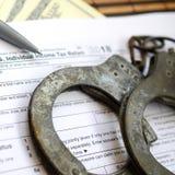 警察手铐在报税表说谎1040 概念的proble 库存图片