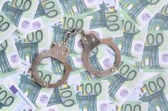 警察把在一套的谎言扣上手铐绿色金钱衡量单位o 免版税库存图片