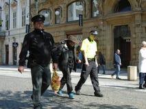 警察拿着无家可归的牛仔 图库摄影