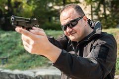 警察指向手枪的保镖枪攻击者 正面图 免版税库存图片