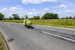 警察摩托车先驱者骑马以速度通过英国乡下 免版税图库摄影