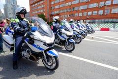 警察摩托车骑士汽车队由自行车游行伴随 免版税库存照片