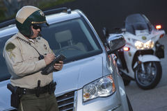 警察文字票,当站立在汽车前面时 免版税库存照片