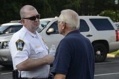 警察谈话与一个老年人 免版税库存图片