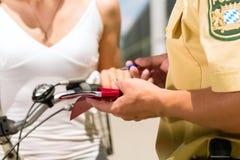 警察-自行车的妇女有警官的 免版税库存照片