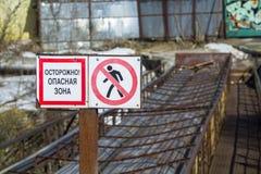 警报信号'小心 危险地带'用俄语 紧急桥梁在背景中 关闭图象 库存照片