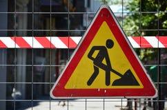 警报信号`建设中`连接有红色和白色镶边信号轻拍的金属滤网篱芭 免版税库存照片