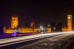 警车和救护车在威斯敏斯特桥梁,伦敦在晚上 免版税库存图片