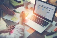 计划一个新的项目的两名妇女在办公室 膝上型计算机和文书工作在桌上 免版税库存照片