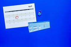 计划一次旅行 买飞机票 在日历附近的票与日期在蓝色背景顶视图拷贝空间盘旋了 库存图片