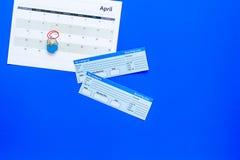 计划一次旅行 买飞机票 在日历附近的票与日期在蓝色背景顶视图拷贝空间盘旋了 库存照片