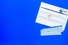 计划一次旅行 买飞机票 在日历附近的票与日期在蓝色背景顶视图拷贝空间盘旋了 免版税库存照片