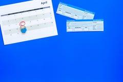 计划一次旅行 买飞机票 在日历附近的票与日期在蓝色背景顶视图拷贝空间盘旋了 免版税库存图片