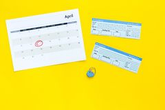 计划一次旅行 买飞机票 在日历附近的票与日期在黄色背景顶视图拷贝空间盘旋了 免版税库存图片